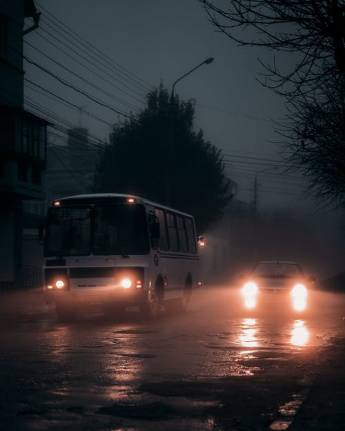 Vehicles driving on wet road in evening