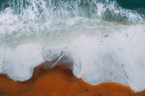 From above of wave of ocean rolling on wet sand of bright beach