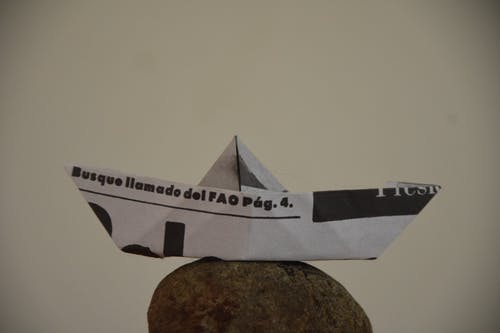 Free stock photo of boat, newspaper, paper boat, stone