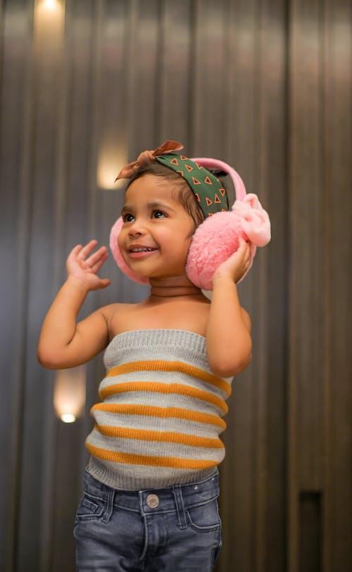 Positive little girl in pink earmuffs near ribbed wall
