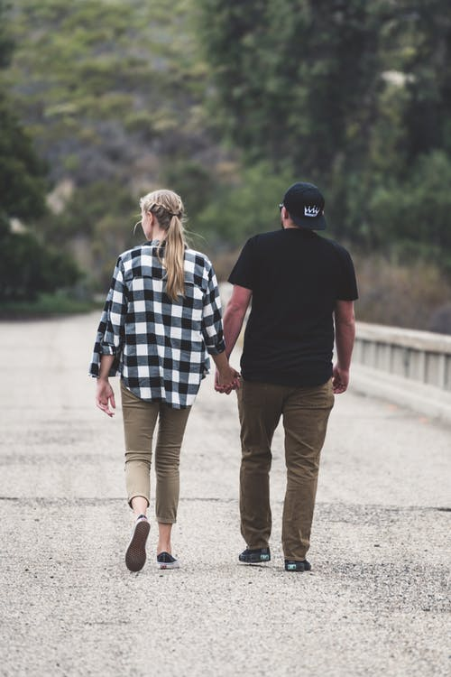 Man and Woman Walking on Road