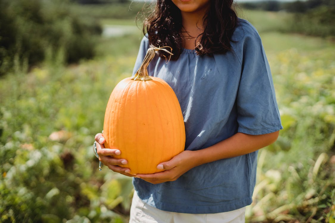 Crop young girl with fresh pumpkin