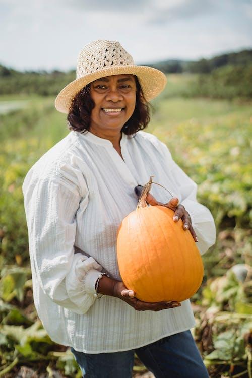 Happy Hispanic woman holding pumpkin in field