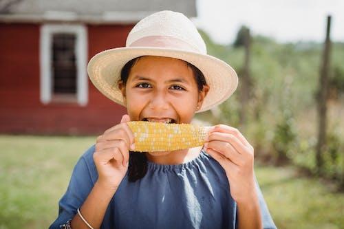 Cheerful Hispanic girl in hat biting tasty appetizing corn while spending summer day in yard