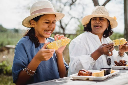 Ethnic funny girl eating with mother in backyard