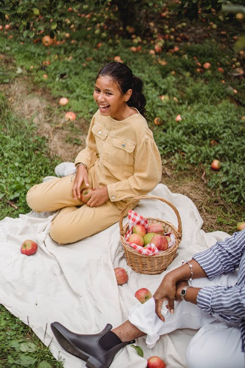 From above of cheerful Hispanic teenager having fun at picnic with mother in orchard with apple trees