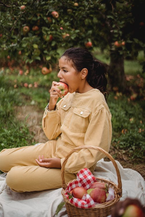 Hispanic teenage girl biting fruit while having picnic with basket of apples in green garden with green plants