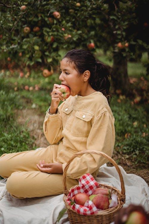 этническая девочка подросток сидит на одеяле и ест яблоко