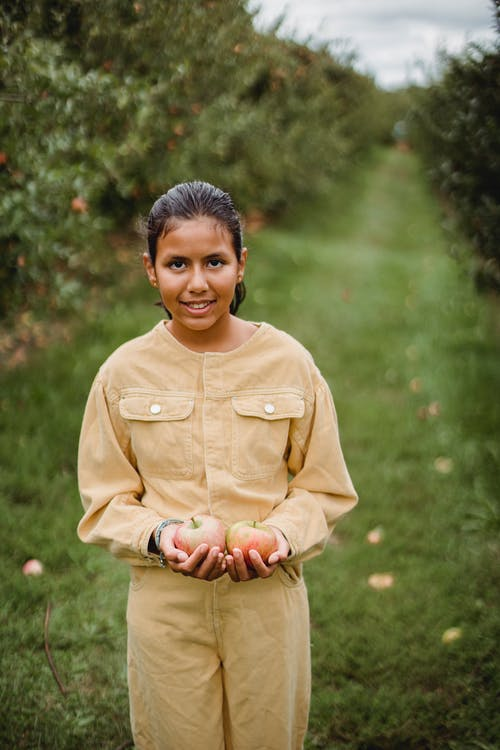 Smiling ethnic girl with handful of apples