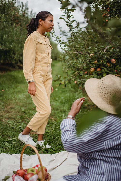 Side view of disappointed Hispanic teen girl standing on grass near apple trees during picnic with mother