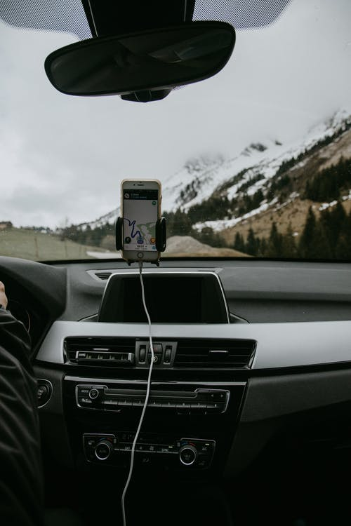 Driver in car with smartphone showing route due to GPS against snowy hill slope with coniferous trees and road