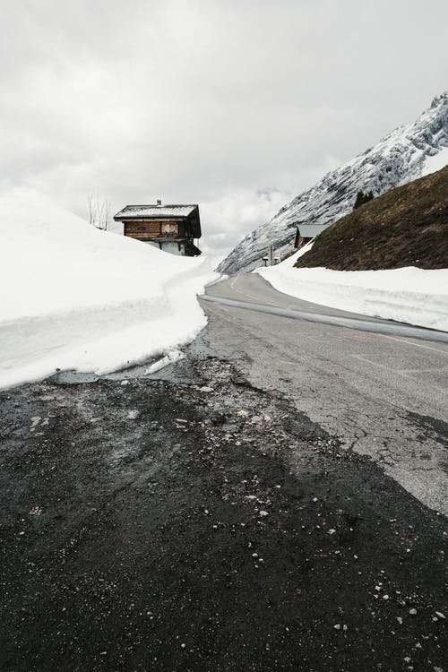 Asphalt road through snowy valley with houses