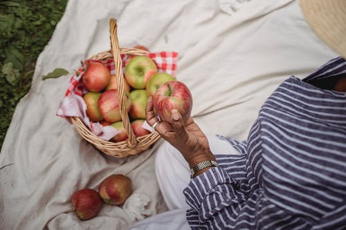 From above of crop ethnic female with ripe apple sitting on plaid while having picnic in nature