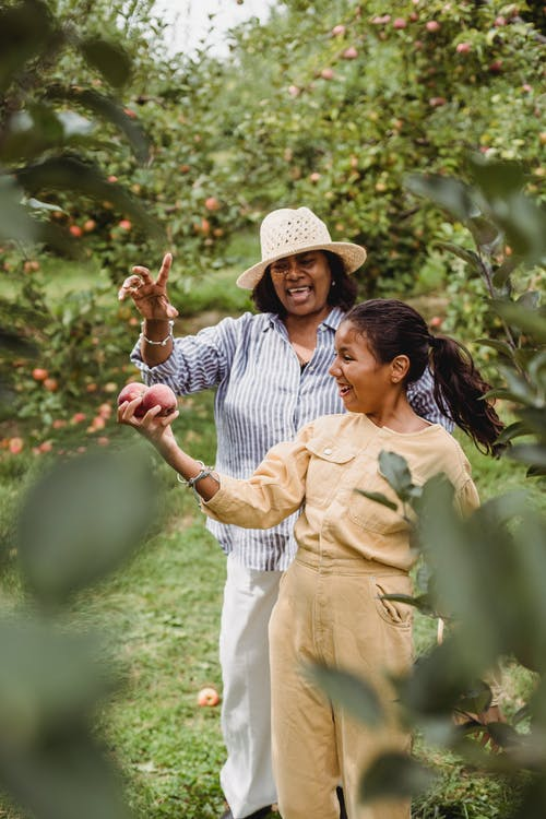 Happy Hispanic woman and young girl with apples