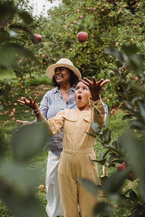 西班牙裔女人和年輕女孩在果園裡微笑