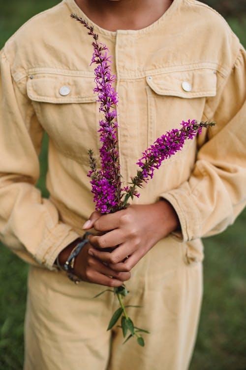 作物與紫色的花的民族女孩