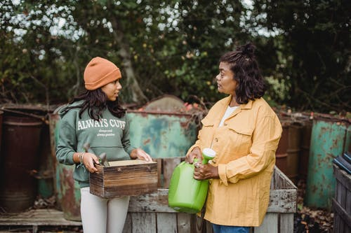 Ethnic woman with watering can speaking with teen near metal containers while looking at each other on farm