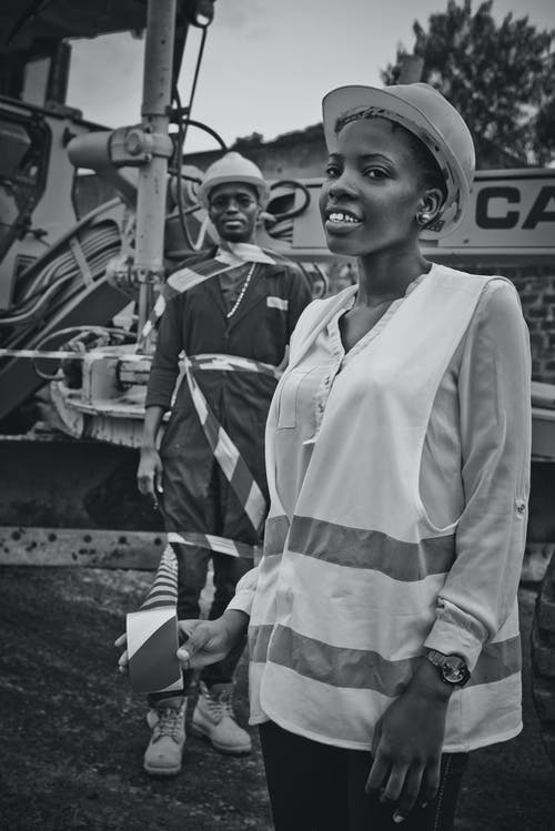 Black and white African American colleagues with warning tape having fun at construction site