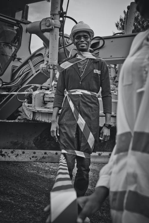 Black and white positive male African American mechanic in uniform wrapped in warning tape standing near excavator