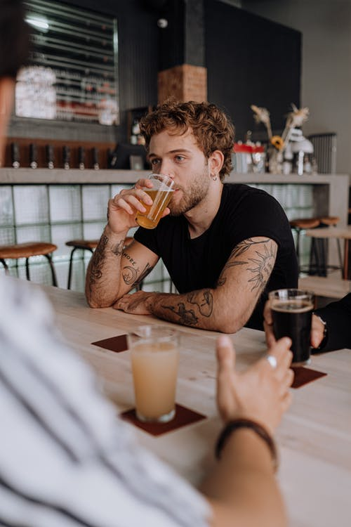 Man in Black Crew Neck T-shirt Drinking Beer