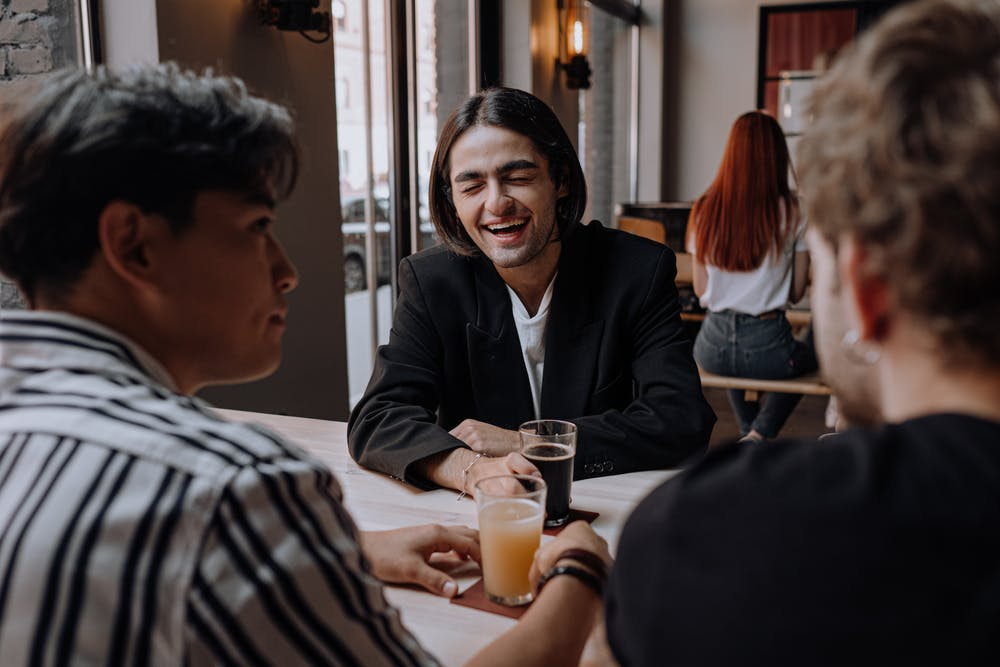 Three male friends enjoying drink at a bar. | Photo: Pexels