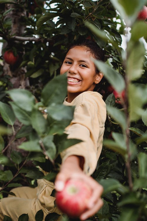 Charming ethnic girl showing ripe apple among tree branches