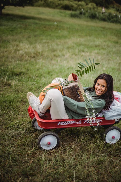 Ethnic girl with box and pumpkin in garden cart
