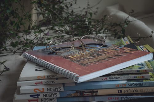 Student books with notepad and glasses
