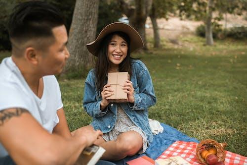 Asyalı çift Kitaplarla Piknik Alanında