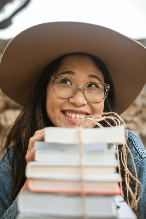 Smiling Woman in Blue Denim Jacket Holding White Book