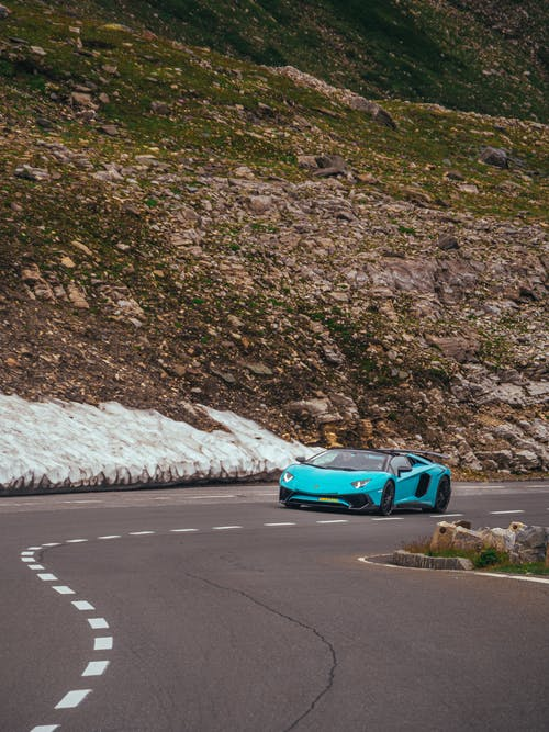 Blue sports car riding on road among mountains