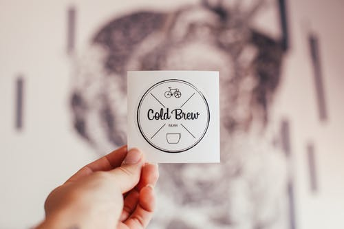 Unrecognizable person demonstrating coffee shop badge with Cold Brew inscription and creative design in hand while standing on blurred background