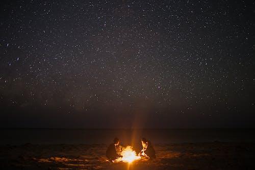 Unrecognizable couple near bonfire on coast at night sky