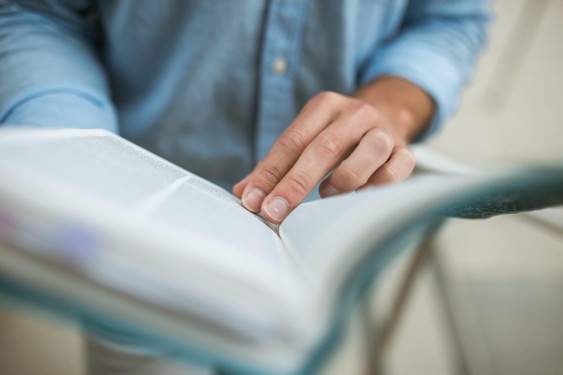 Pessoa Com Camisa De Manga Comprida Azul Segurando Um Livro Branco