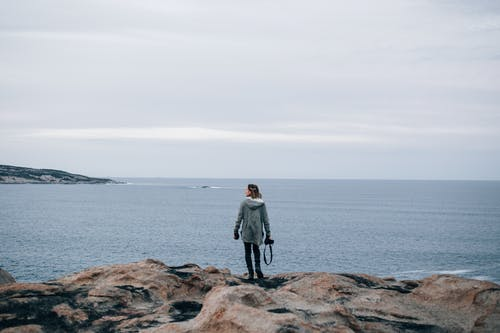 Woman in Gray Coat Standing on Brown Rock Near Body of Water