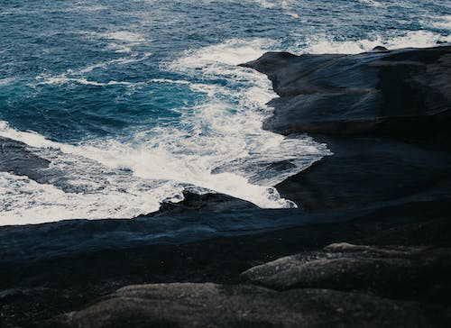 Ocean Waves Crashing on Black Rock Formation