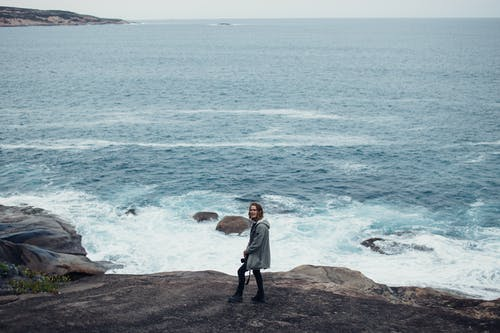Woman in White Long Sleeve Shirt and Black Pants Standing on Brown Rock Near Body of Near on Near on