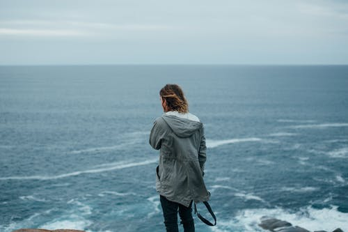 Woman in Gray Jacket Standing on Seashore