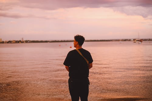 Man in Black Shirt Standing on Seashore