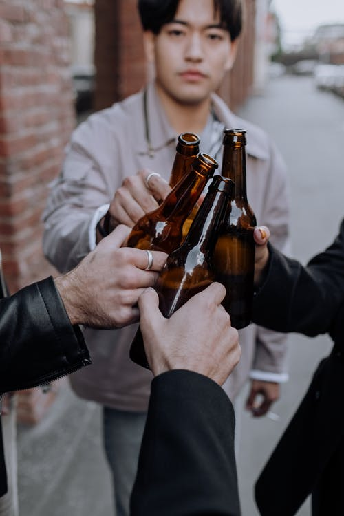 Person Holding Brown Glass Bottles