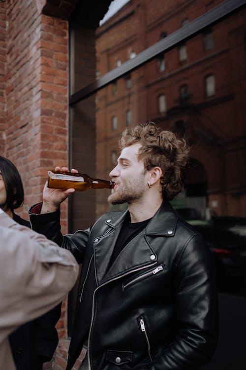 Man in Black Leather Jacket Drinking Beer