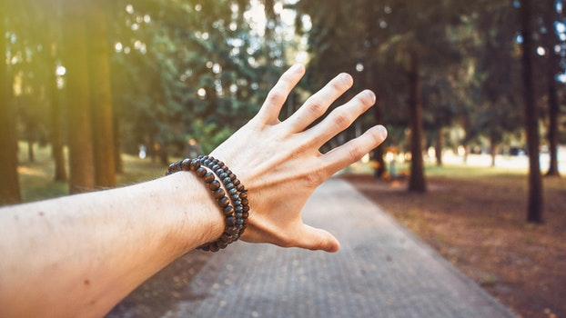 Free stock photo of hand, trees, pavement, bracelet