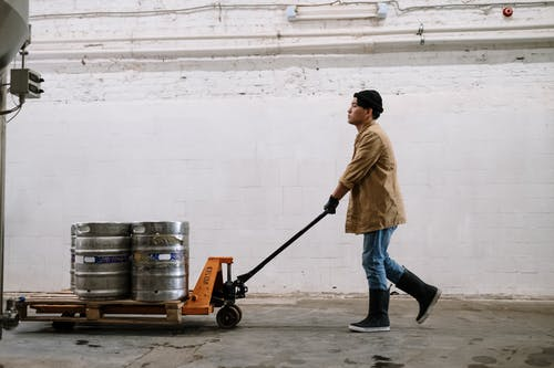 Man in Brown Coat and Blue Denim Jeans Holding Black and Red Hand Truck