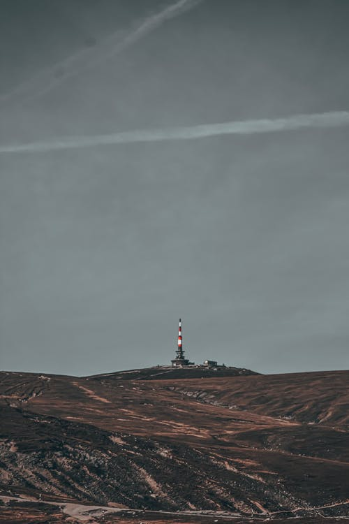 Hills under cloudy gray sky with traces