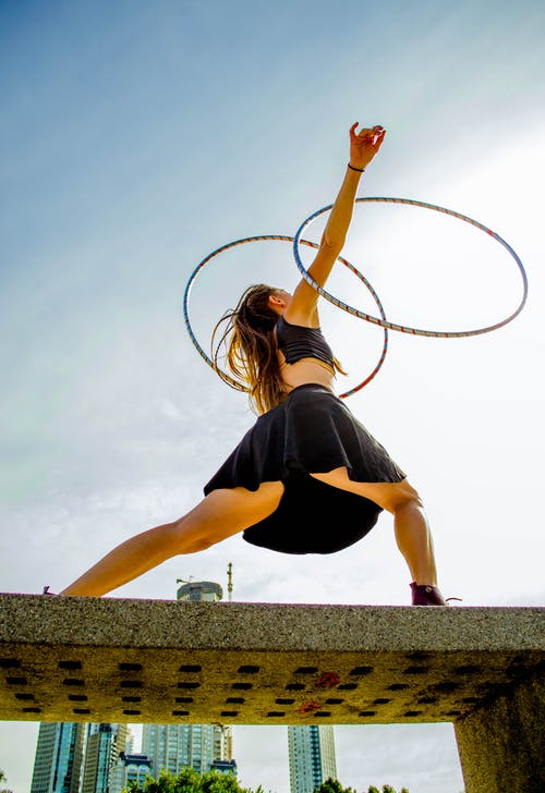 Person Standing on Concrete Bench With Hula Hoops on Her Arms