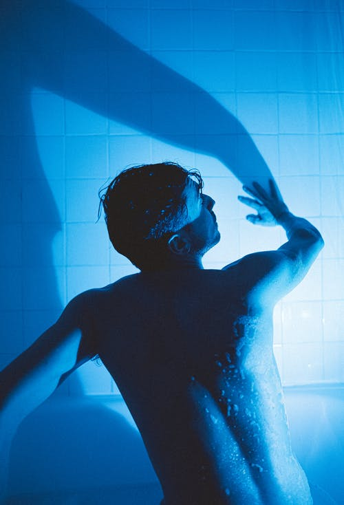 Back view of shirtless man in water drops standing in dark bathroom with blue light