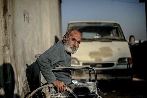 Senior ethnic in wheelchair near concrete wall against car