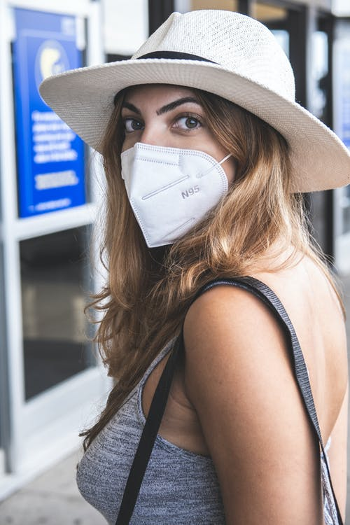 A Woman Wearing a Cowboy Hat and a Face Mask