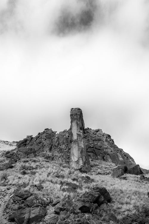 Rocky cliff in mountainous terrain under clouds