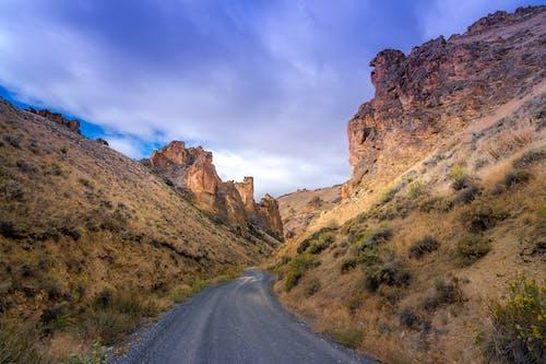 Picturesque view of curvy asphalt roadway running through hills and steep cliffs in mountainous terrain